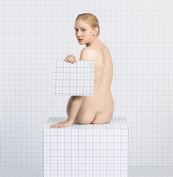 Naked Girl Sitting Down, Turning Towards Camera
